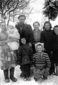 Vlasta Tkadlecová (dole v pruhovaném svetru) s bratrem, babičkou (stojící nad ní), strýcem, tetou a dalšími příbuznými / konec 50. let